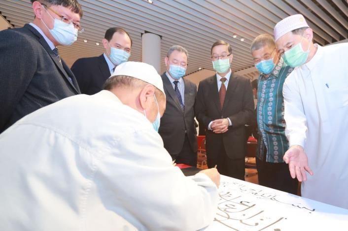 圖二:曹次長(右三)欣賞阿拉伯文書法現場表演。
