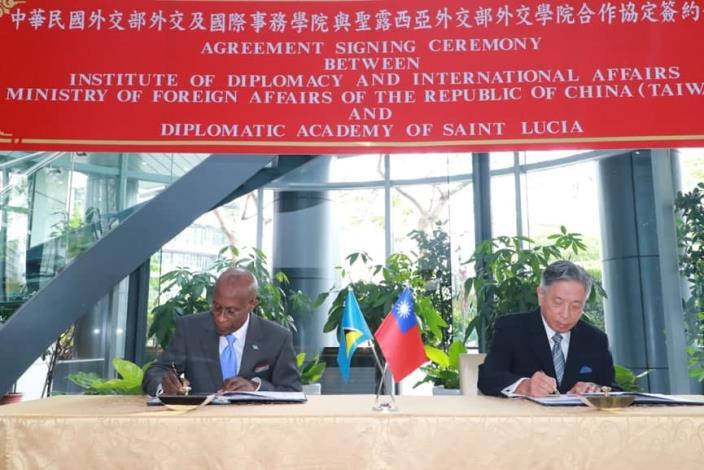Caption[1]: Deputy Minister Tien (right) and Ambassador Laurent (left) sign the agreement.