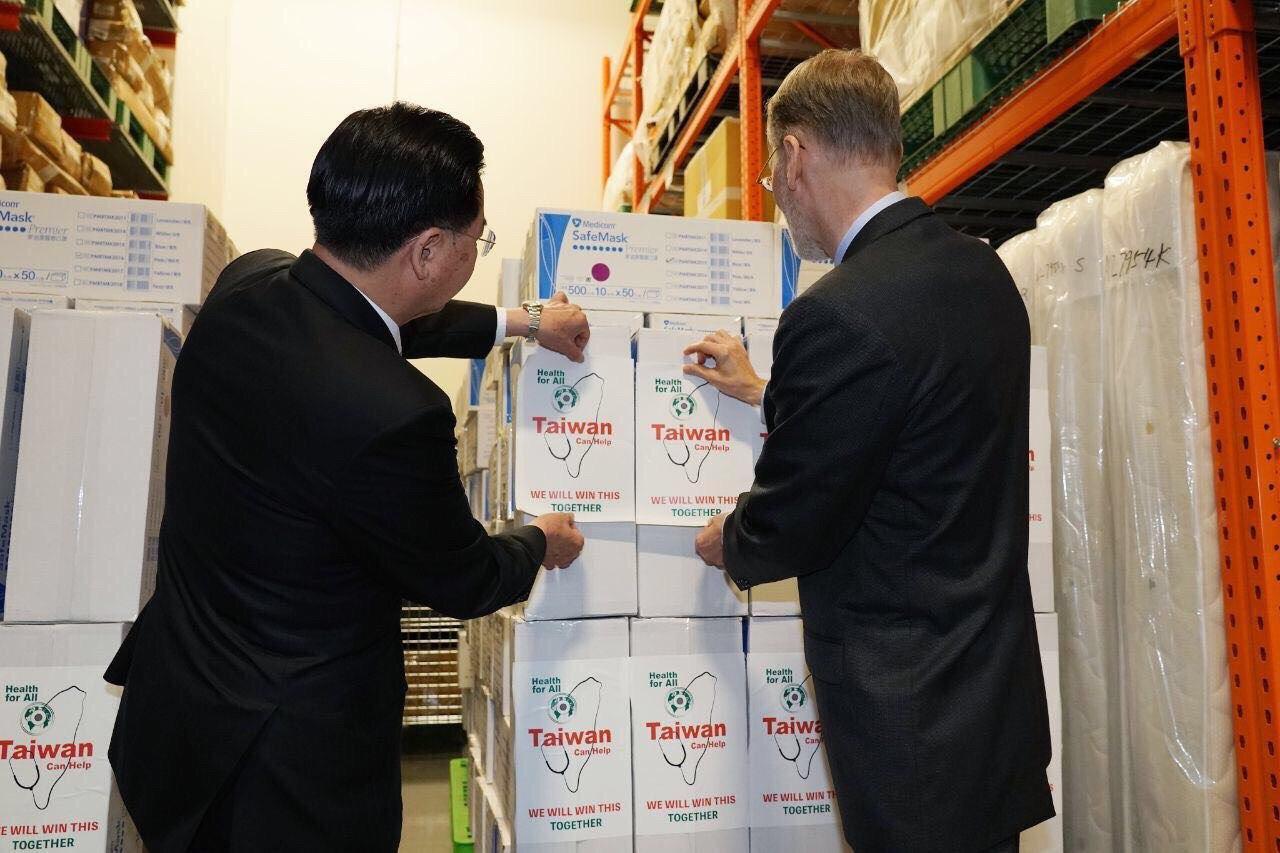 圖一:部長與酈英傑處長共同為在捐贈美國口罩紙箱貼上「Taiwan can help」之貼紙。